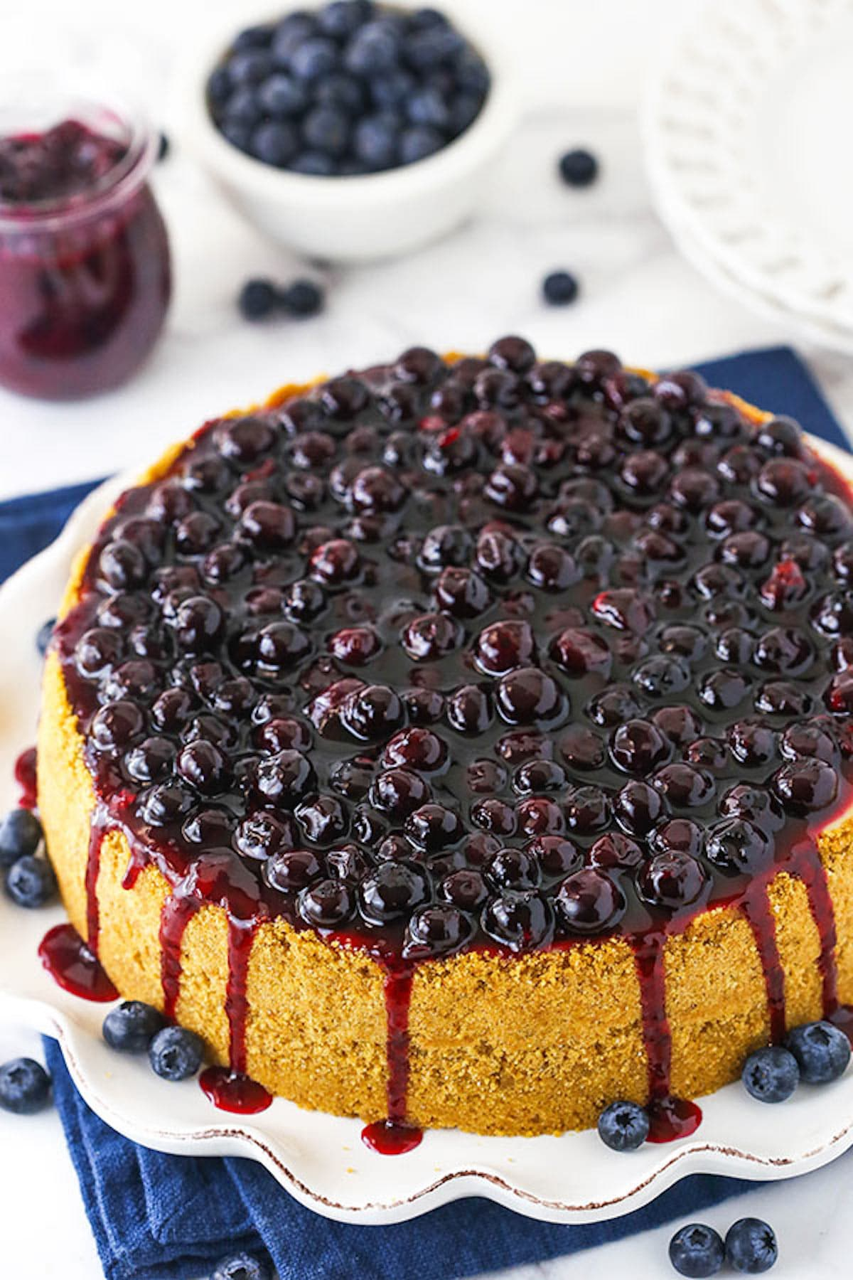 The Top View of a Blueberry Cheesecake with Sauce Dripping Down the Sides of the Cake