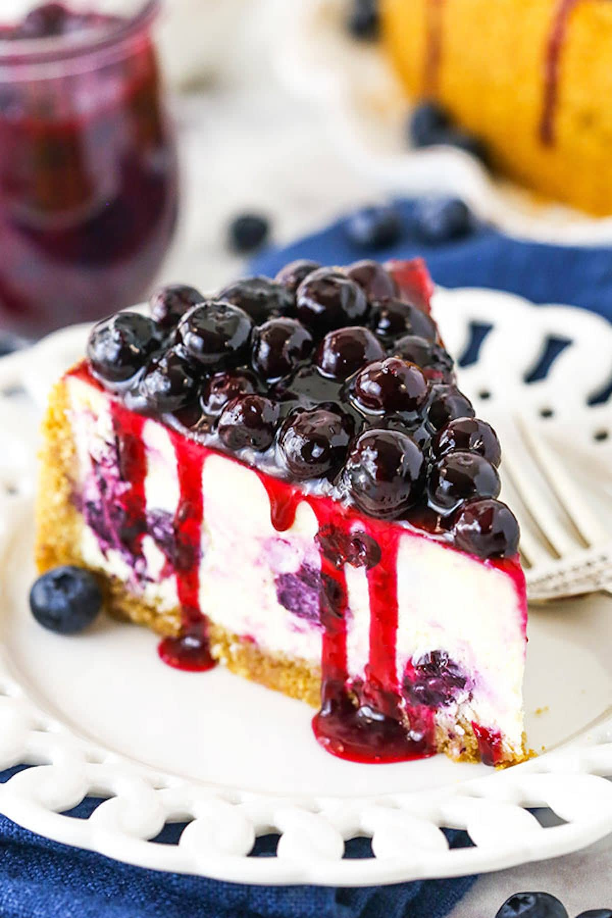 A Close-Up Shot of a Slice of Baked Blueberry Cheesecake with Blueberry Sauce on Top