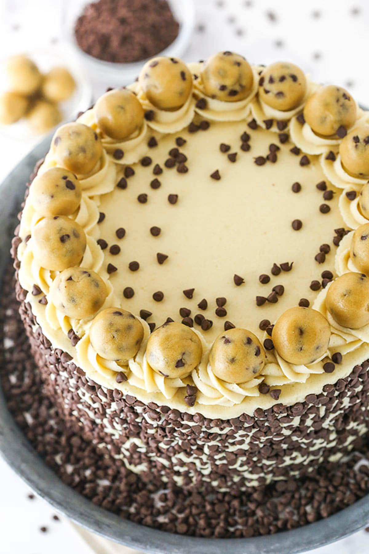 A Cookie Dough Layer Cake with Cookie Dough Frosting, Chocolate Chips and Balls of Dough on Top
