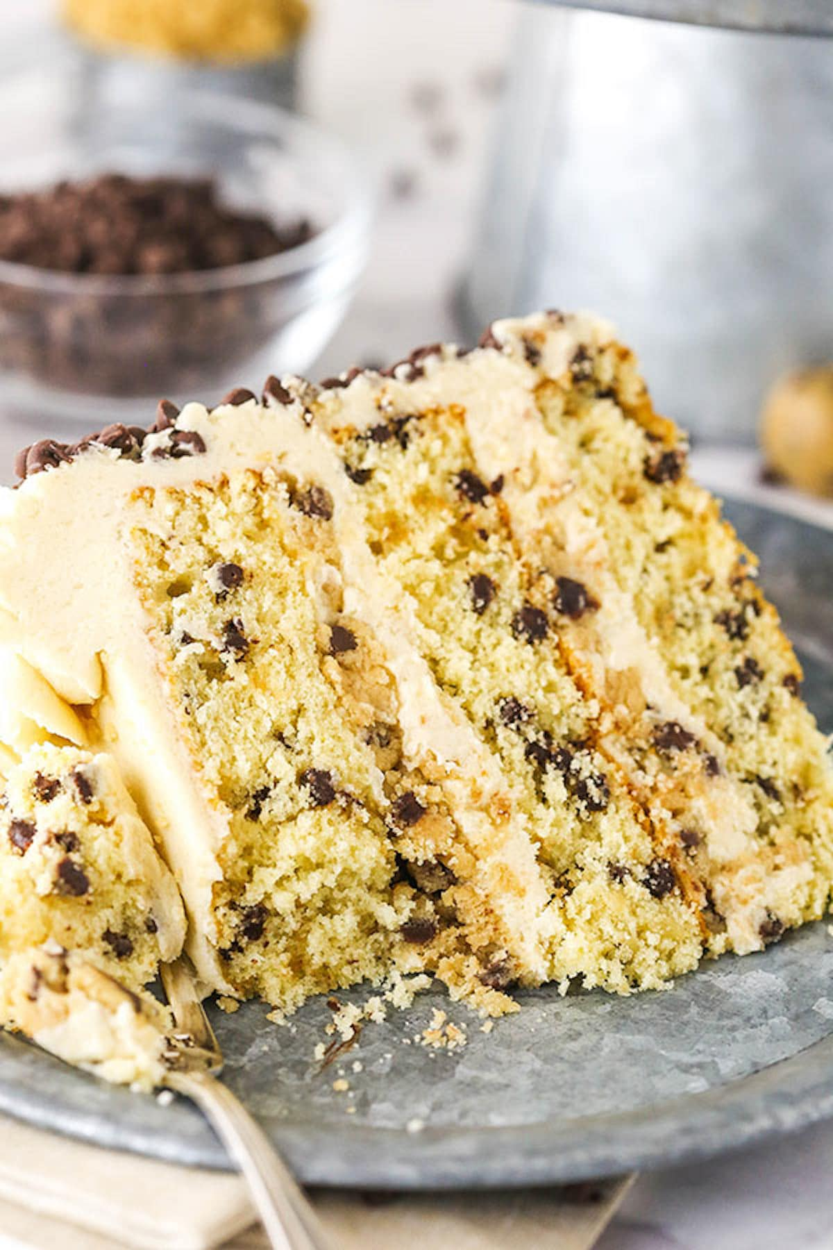 A Slice of Chocolate Chip Cookie Dough Layer Cake on a Metal Plate