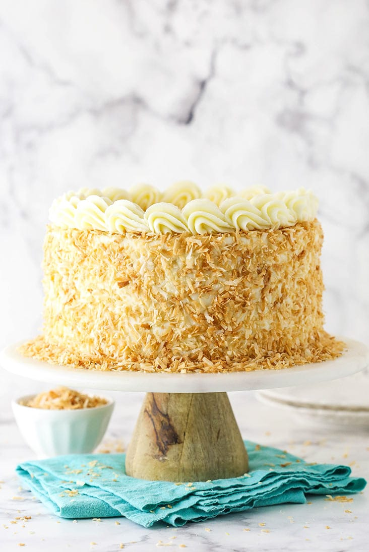 full image of coconut custard cake on wood and marble cake stand