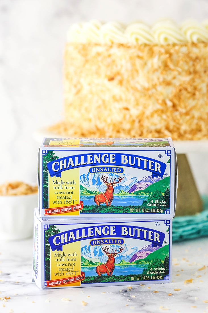 two packages of challenge butter stacked in front of cake