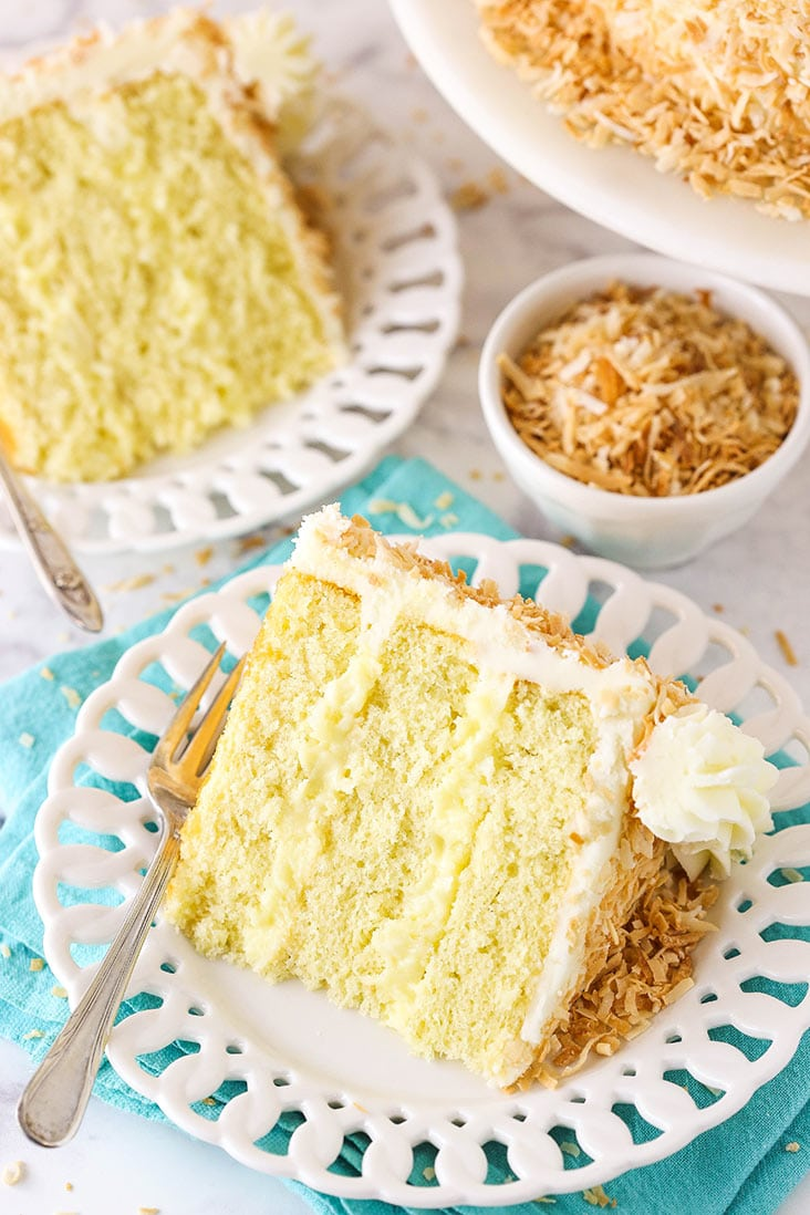 two slices of coconut cake with a bowl of toasted coconut