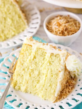 slice of coconut custard cake on a white plate with teal napkin
