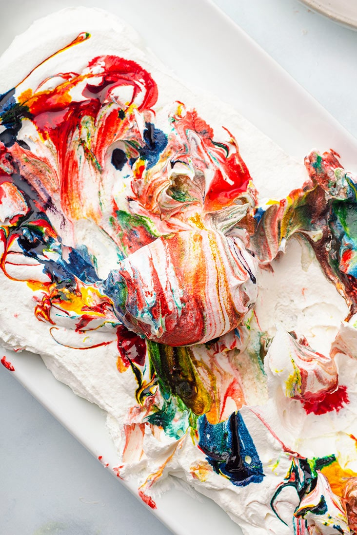egg being rolled in coloring and cool whip
