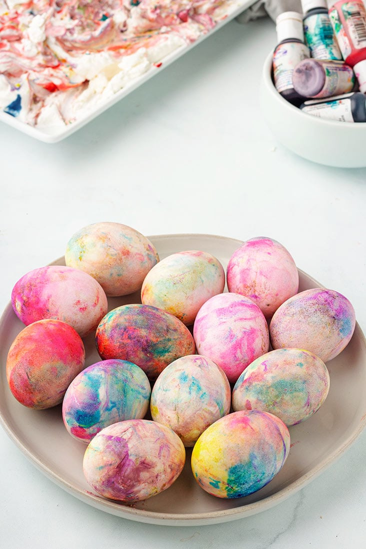 finished eggs on cream plate with coloring and cool whip in the background