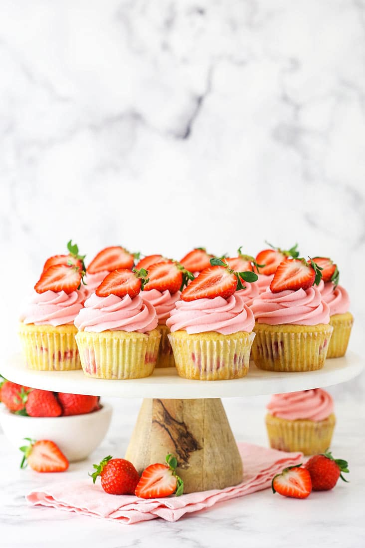 strawberry cupcakes on a marble stand and pink napkin