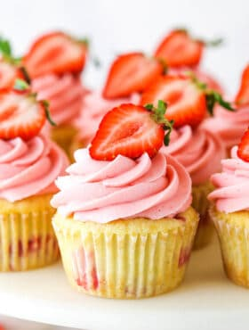 strawberry cupcake on a cake stand with other cupcakes around