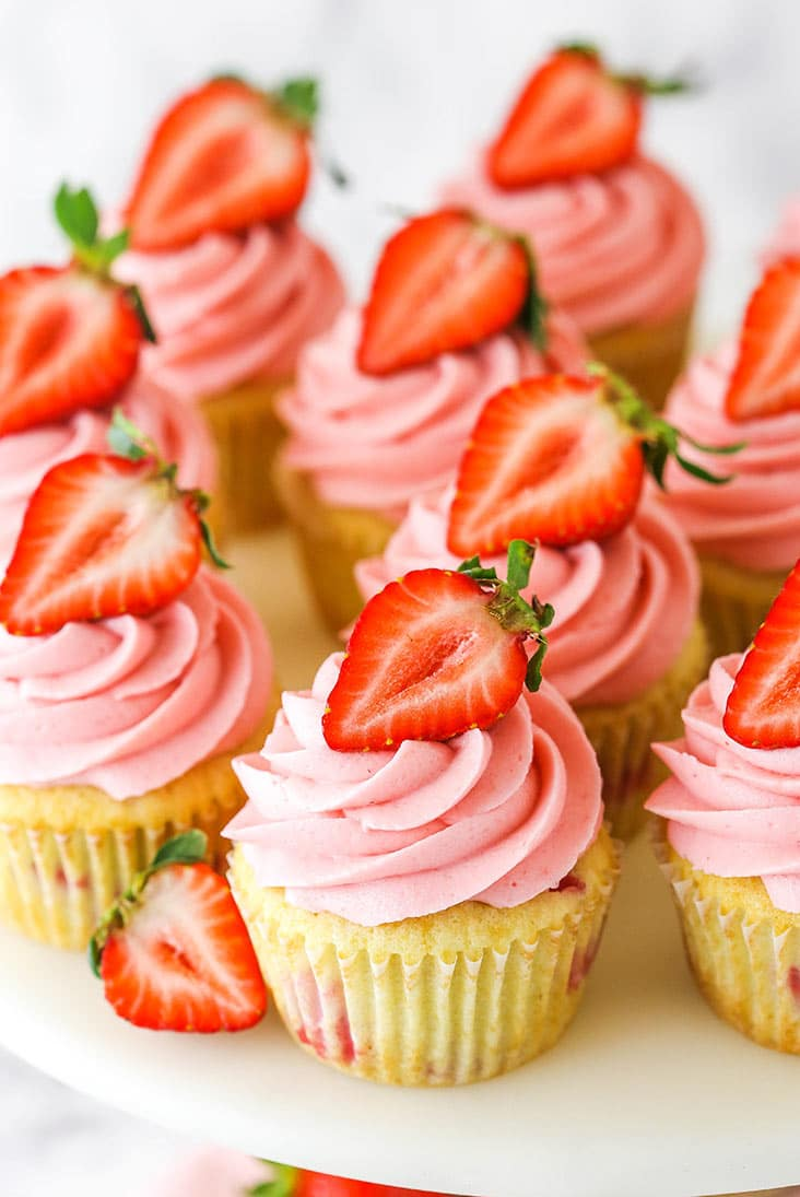 bunch of strawberry cupcakes on the top of a cake stand