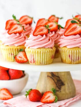 fresh strawberry cupcakes on marble and wood cake stand with strawberries around base