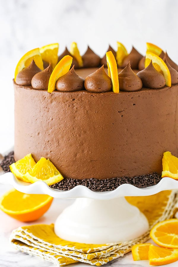 full orange chocolate cake on a white cake stand with orange slices
