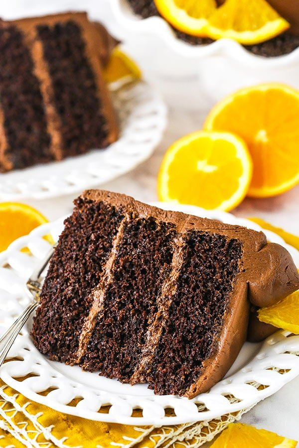 two orange chocolate cake slices on white plates with oranges in background