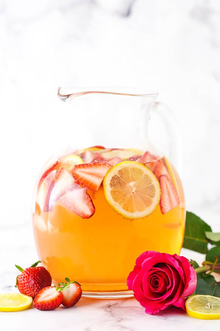 A pitcher of Rosewater Rosé Sangria with a red rose in front
