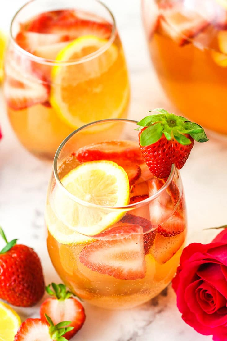 A glass of Rosewater Rosé Sangria garnished with a fresh strawberry