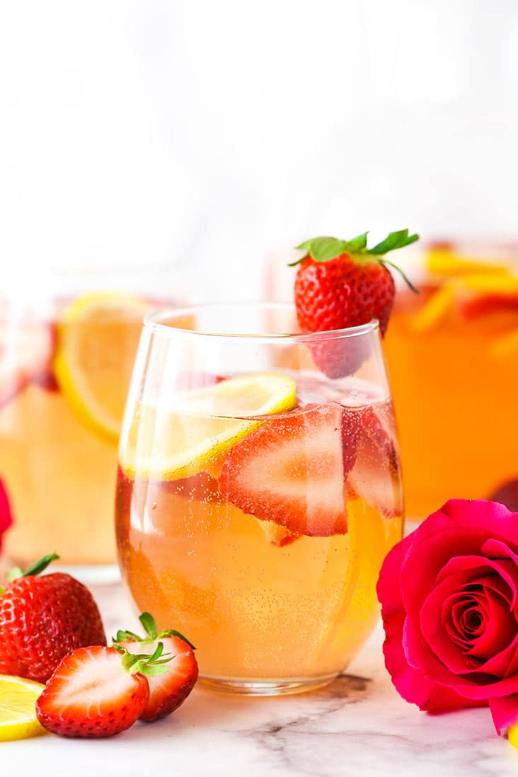 3 glasses of rosewater sangria, garnished with a fresh streberry and rose.