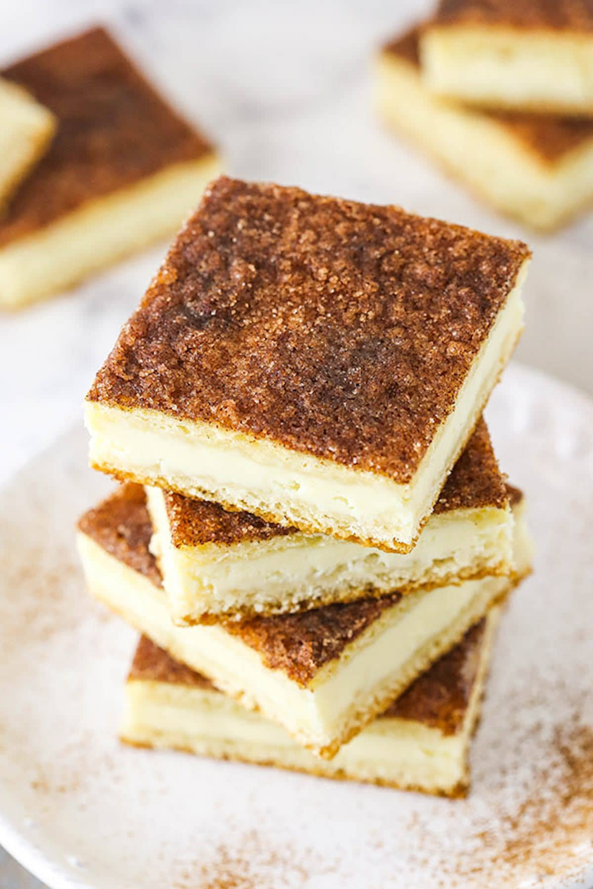 Four Cinnamon Sugar Cheesecake Bars Stacked on a White Plate