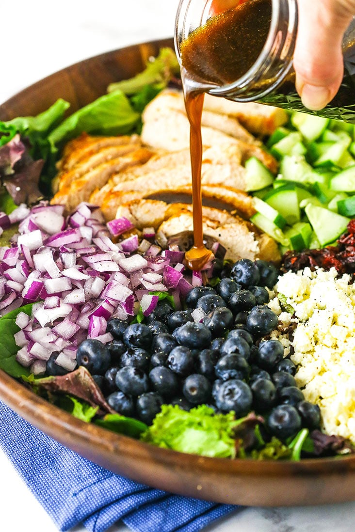 Balsamic vinaigrette being poured over a bowl over chicken blueberry feta salad