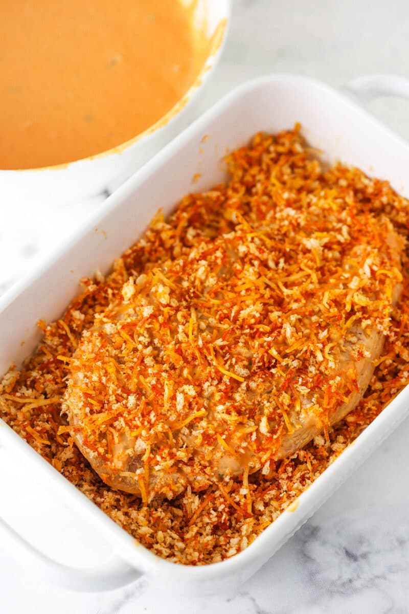 Chicken sitting in panko mixture with panko mixture all over it