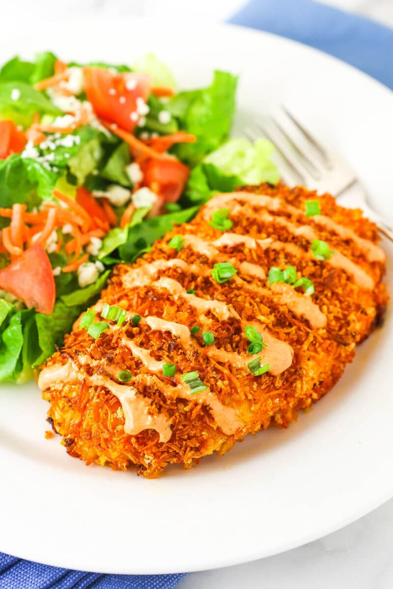 Crispy Buffalo chicken and salad on white plate