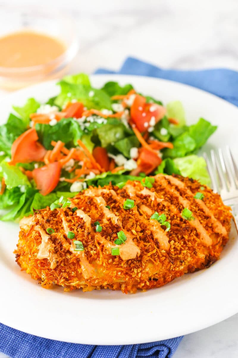 Crispy Buffalo Chicken with salad on white plate and blue napkin