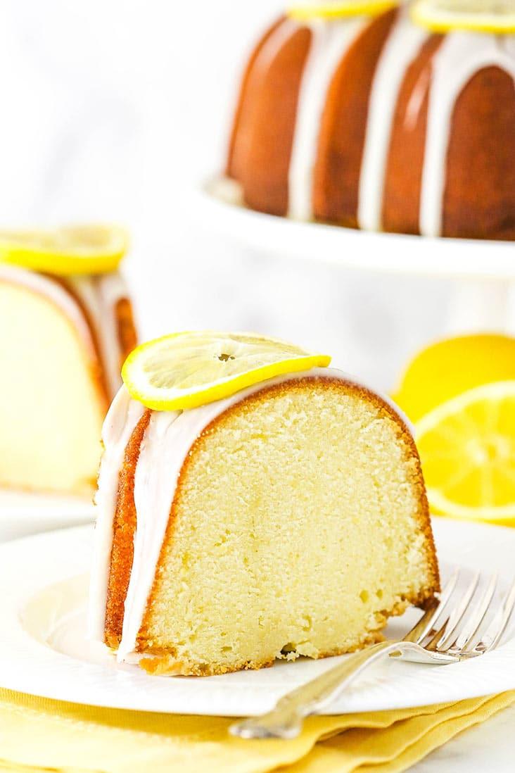 A slice of lemon pound cake on a white plate, garnished with a lemon slice.