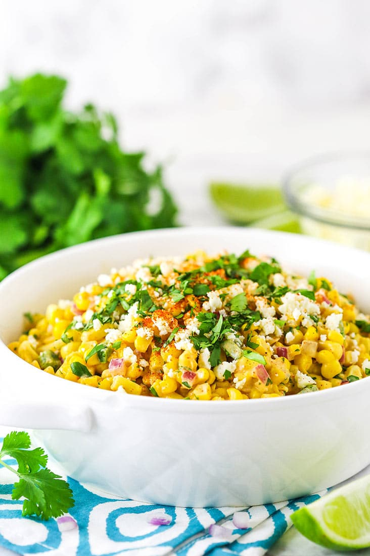 mexican street corn salad in white dish from the side with cilantro in the background