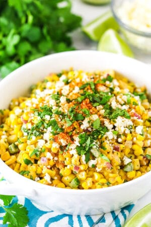 mexican street corn salad in a white bowl on a teal and white napkin