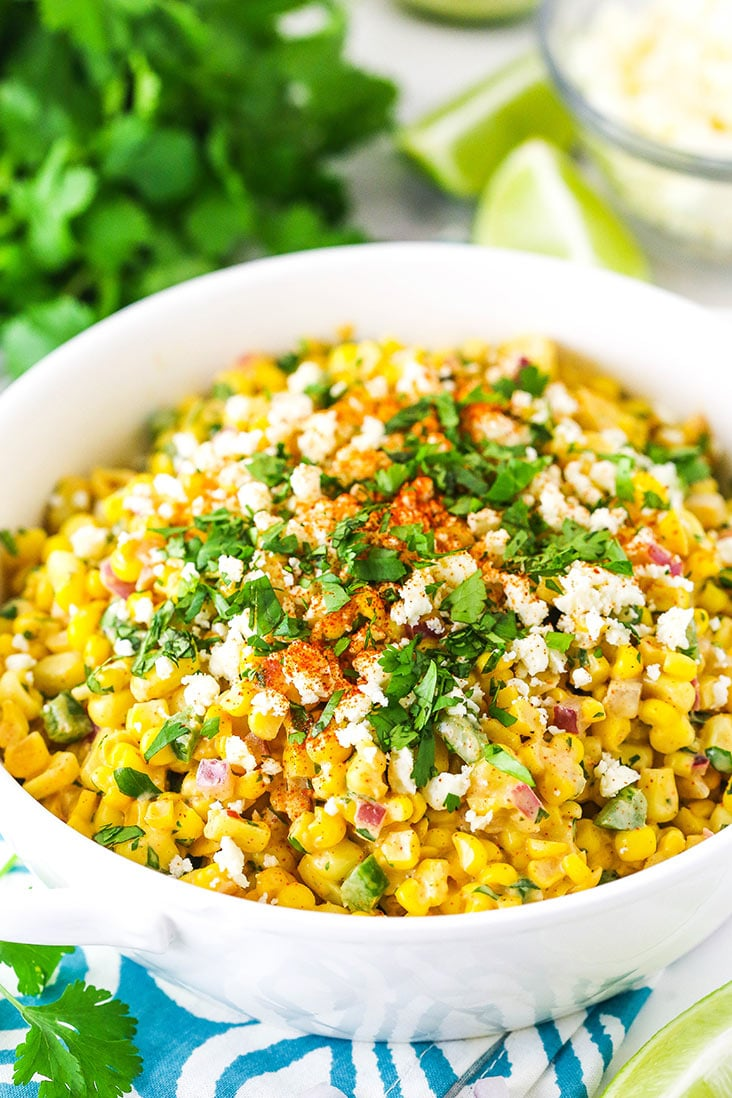mexican street corn salad in white bowl on teal and white napkin