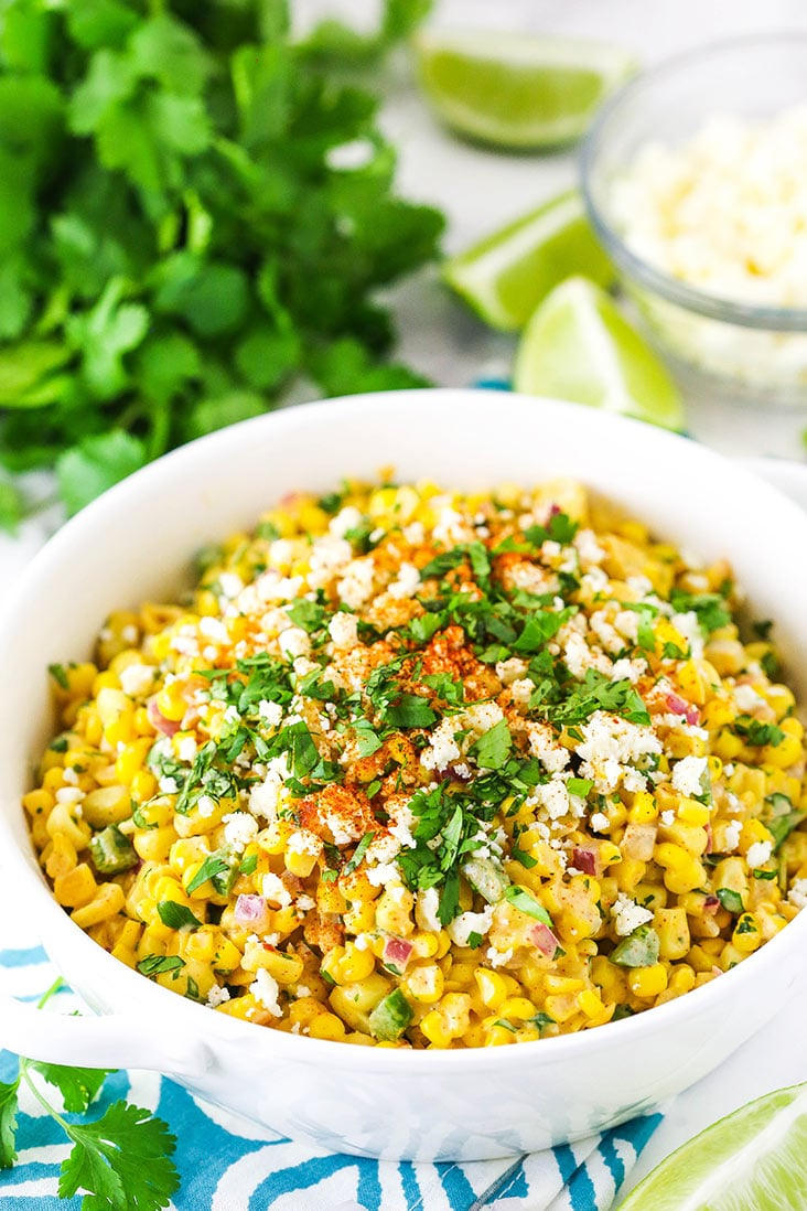 corn salad in a white dish with cilantro in the background