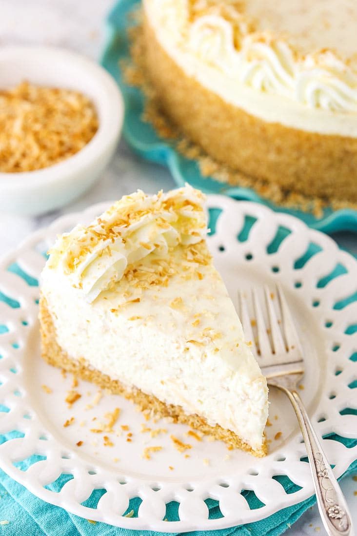 A slice of toasted coconut cheesecake with coconut whipped cream