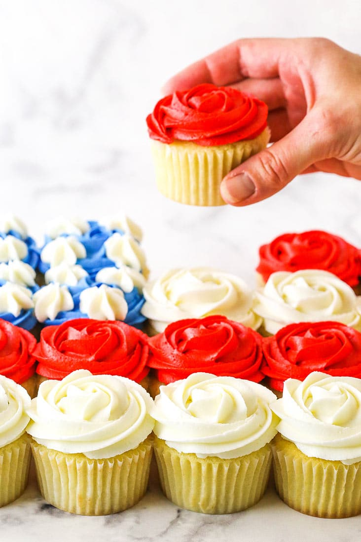 hand lifting a red cupcake out of flag formation