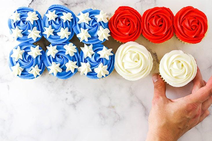 hand putting together the flag cupcake cake