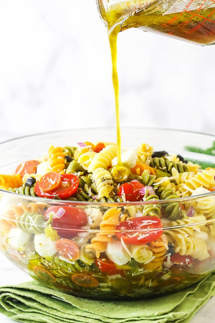 Italian dressing being poured over pasta with vegetables in a glass dish