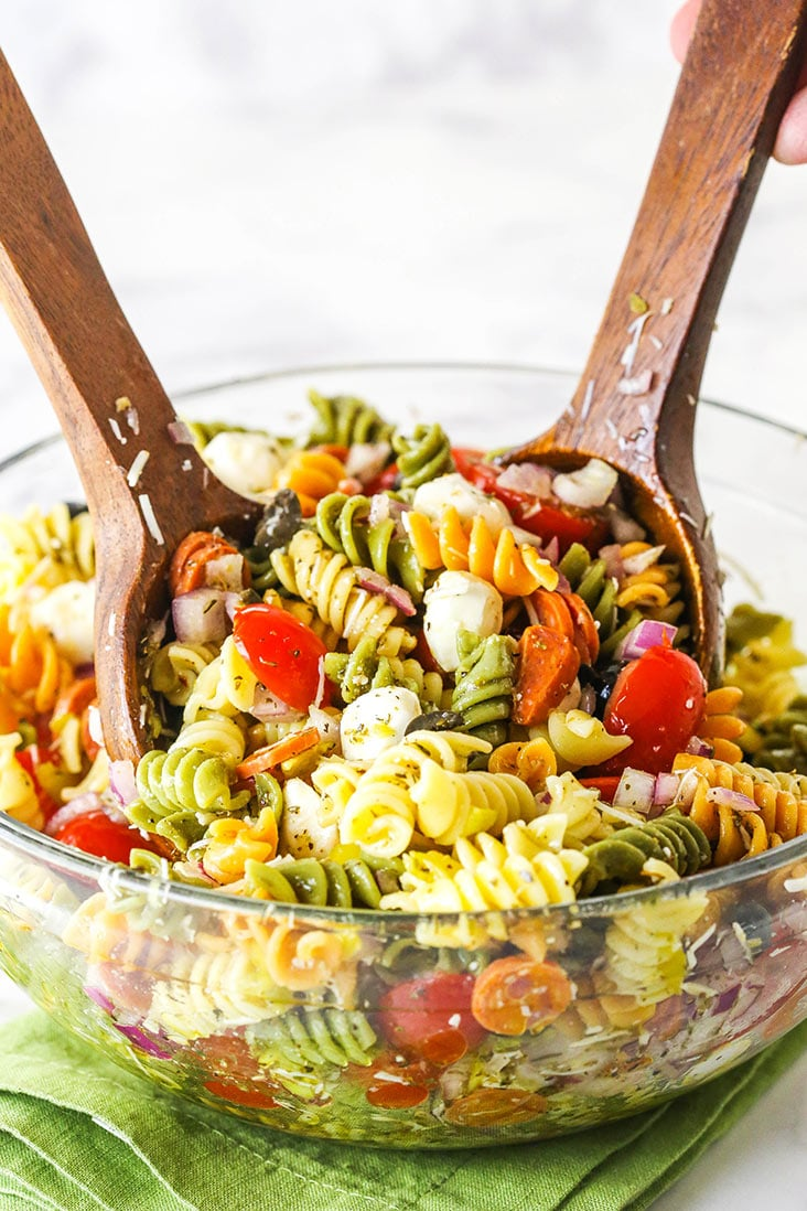 Two wooden spoons mixing a big bowl of Italian pasta salad