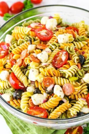 A bowl of Italian pasta salad with fresh mozzarella, tomato, olives, and pepperoni