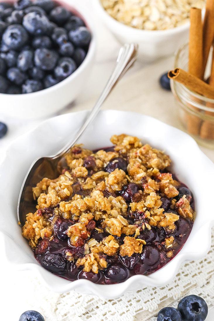 blueberry crisp in a white ruffled bowl