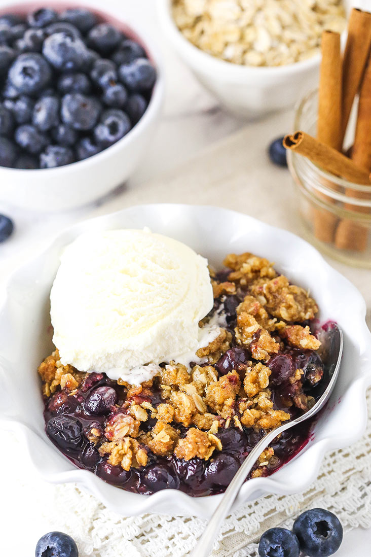 blueberry crisp with a scoop of ice cream in white bowl with blueberries, oats and cinnamon sticks in background
