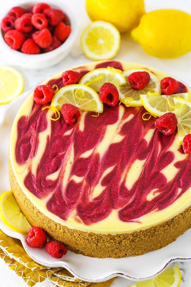 A lemon raspberry swirl cheesecake topped with fresh raspberries and lemon slices