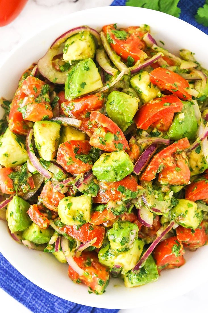 Tomatoes, avocados, and onion mixed together in a bowl
