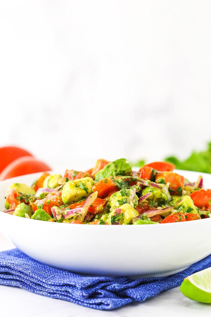 A white bowl of tomato avocado salad