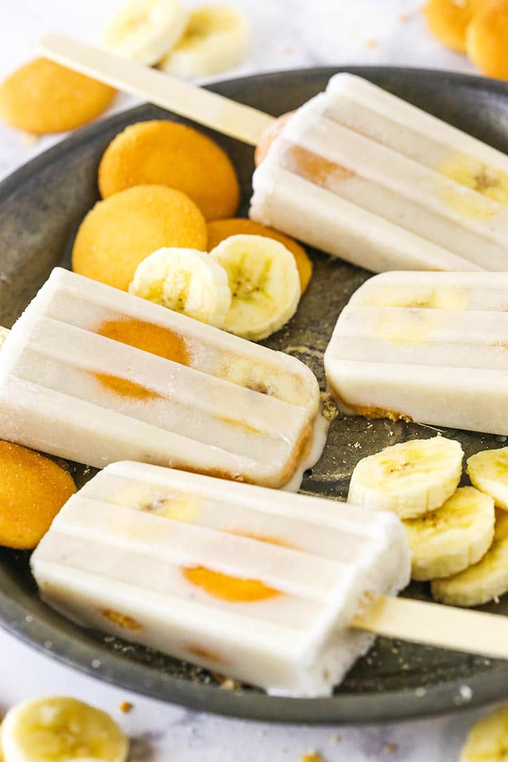 Banana popsicles on a tray with vanilla wafers and banana slices