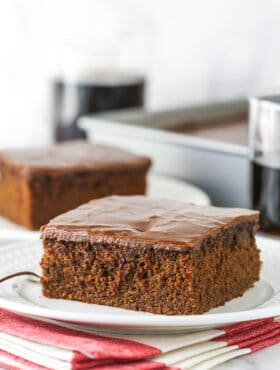 slice of coca cola cake on white plate with glass of coke in background