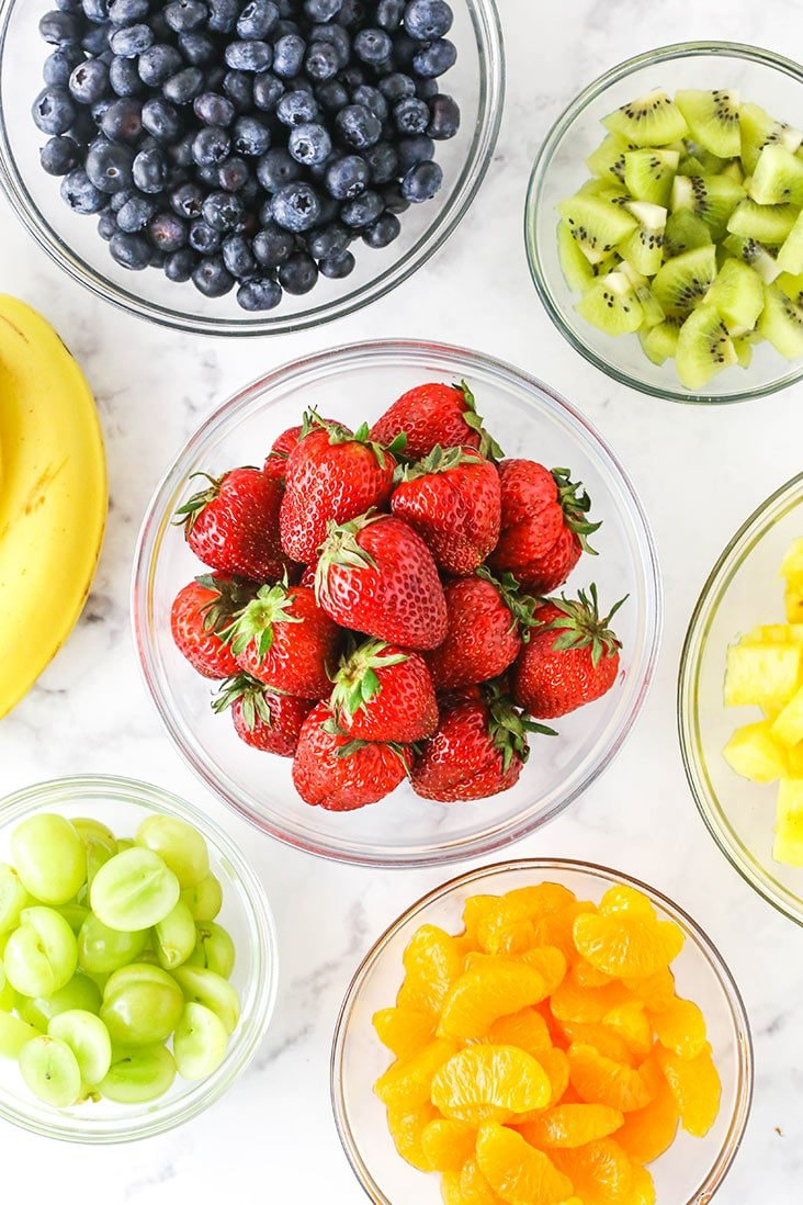 all the different chopped fruits in separate bowls - strawberries, blueberries, kiwi, grapes, oranges, pineapple and bananas