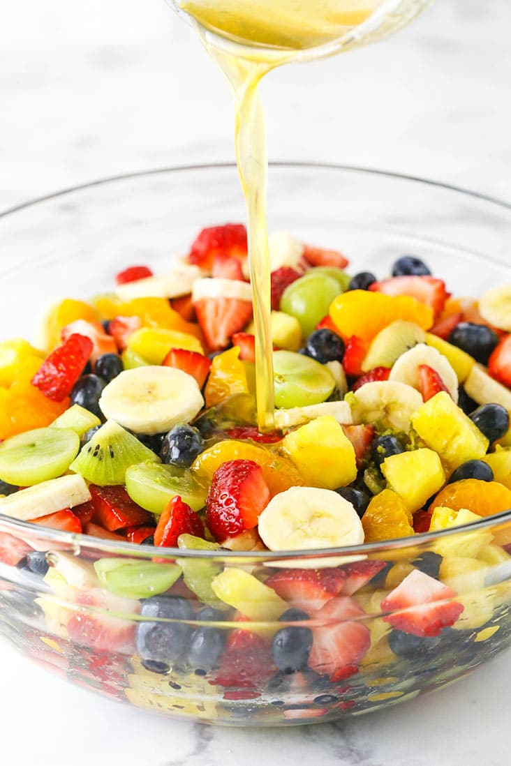 chopped fruit in a clear bowl with dressing being poured on it