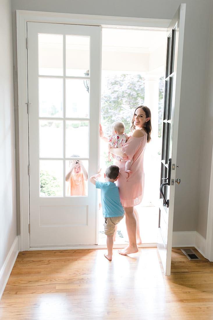 Lindsay walking through an open front door with the kids
