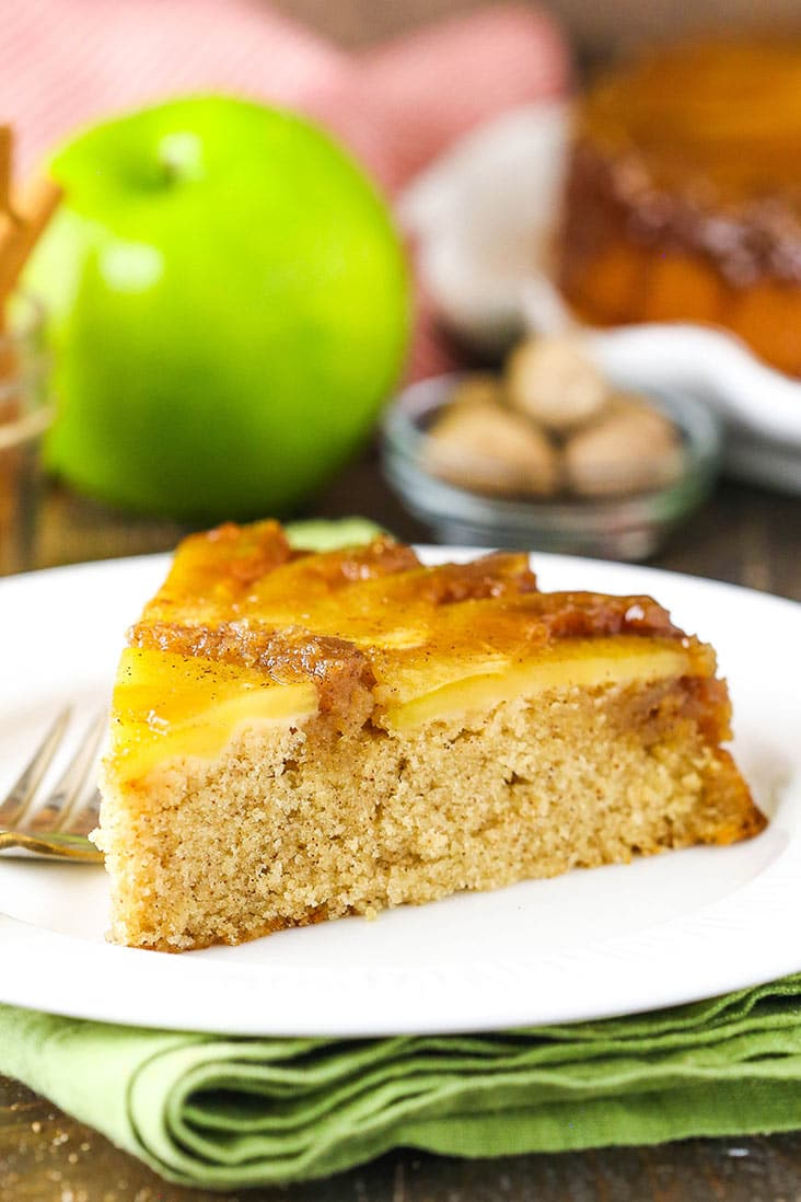 A slice of apple upside down cake on a white plate