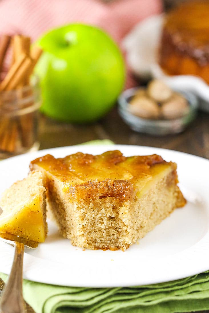 A slice of apple upside down cake on a white plate with a bite missing