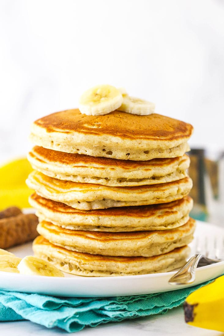 A stack of fluffy pancakes topped with banana slices