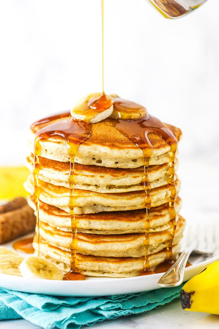 A stack of fluffy banana pancakes with syrup being poured over the top