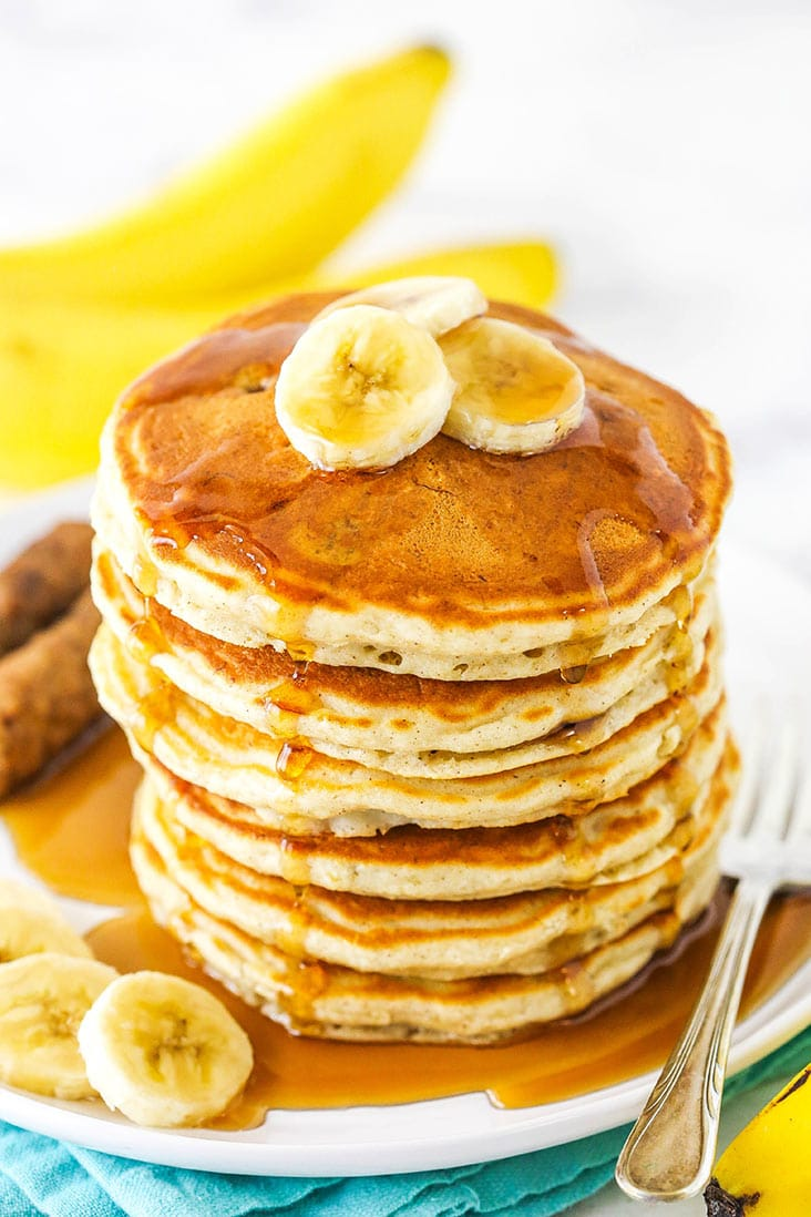 Banana pancakes stacked high on a plate with syrup and banana slices